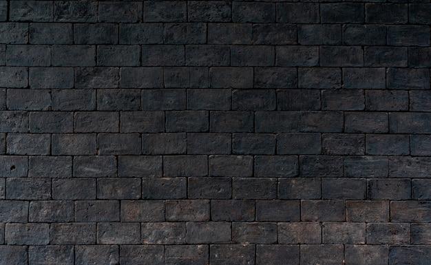 Fundo áspero preto e marrom da textura da parede de tijolo. parede de tijolo escura para afligir-se emocional. arquitetura exterior.