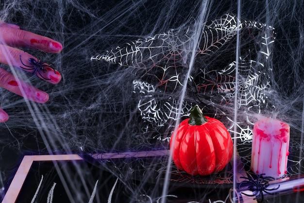 Fundo assustador de halloween com as mãos ensanguentadas, abóboras, teias de aranha, aranhas