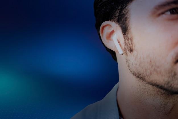 Fundo azul com americano ouvindo música em fones de ouvido sem fio