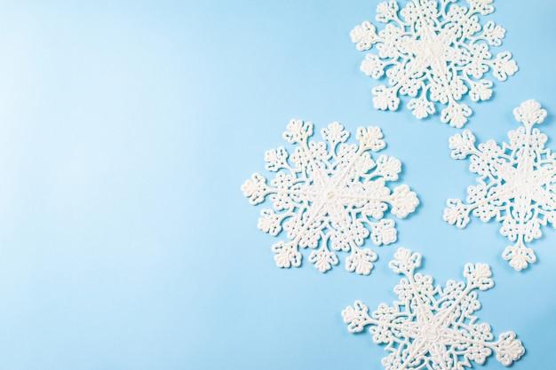 Fundo azul com borda de flocos de neve cintilante. configuração aérea plana com espaço para texto