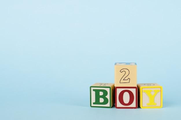 Fundo azul com cubos coloridos com letras menino e número
