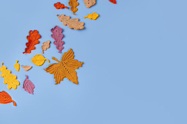 Fundo azul com folhas amarelas de tricô. conceito de outono. clima de outono