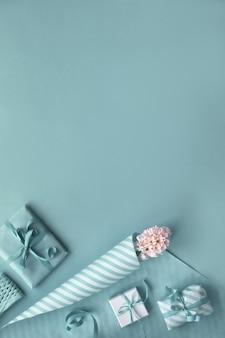Fundo azul com jacinto rosa, papel de embrulho e caixas de presente