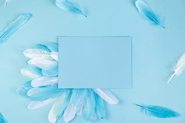 Fundo azul com penas e papel para anotações, copyspace.