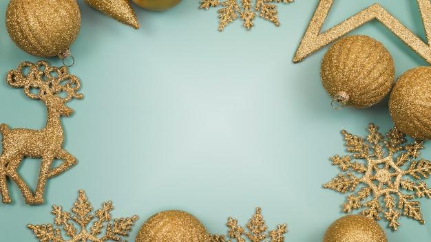 Fundo azul de ano novo e natal com bolas douradas brilhantes, flocos de neve e veados
