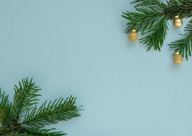Fundo azul de natal com galhos de árvores de abeto e pequenas bolas de ouro.