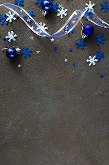 Fundo azul de natal. fita encaracolada com bolas decorativas e flocos de neve.