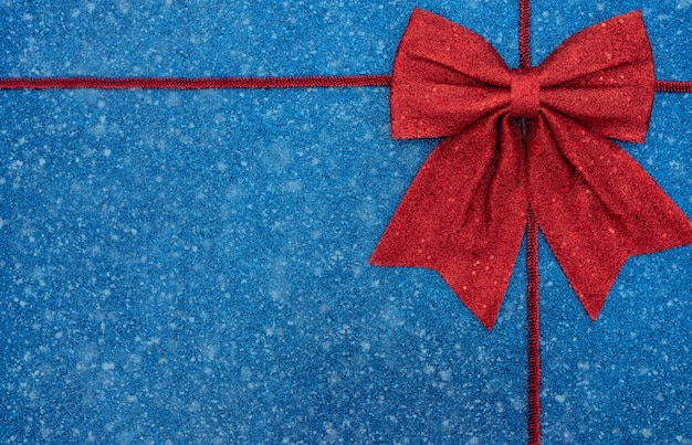 Fundo azul de natal ou inverno com enfeites vermelhos, arco e neve. estilo liso leigo com espaço de cópia.