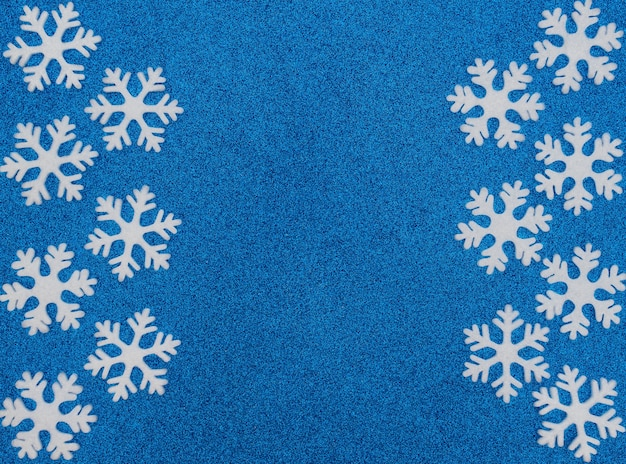 Fundo azul de natal ou inverno com flocos de neve brancos. cartão de ano novo.