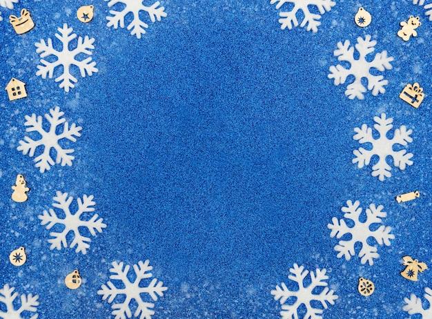 Fundo azul de natal ou inverno com flocos de neve brancos e enfeites de madeira