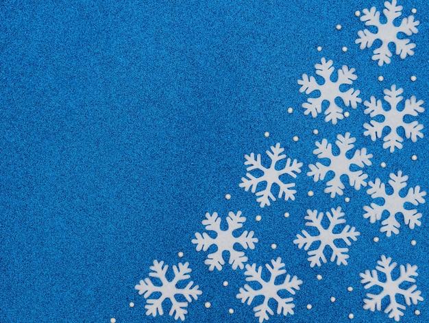 Fundo azul de natal ou inverno com flocos de neve brancos e miçangas. estilo liso leigo com espaço de cópia.