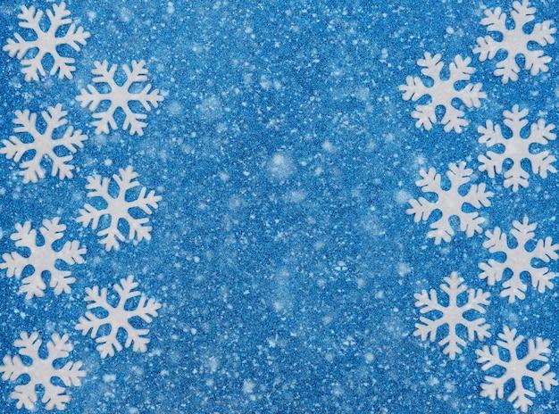 Fundo azul de natal ou inverno com flocos de neve brancos e neve. estilo liso leigo com espaço de cópia.