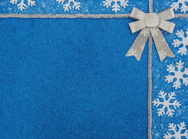 Fundo azul de natal ou inverno com flocos de neve brancos, enfeites de prata e arco