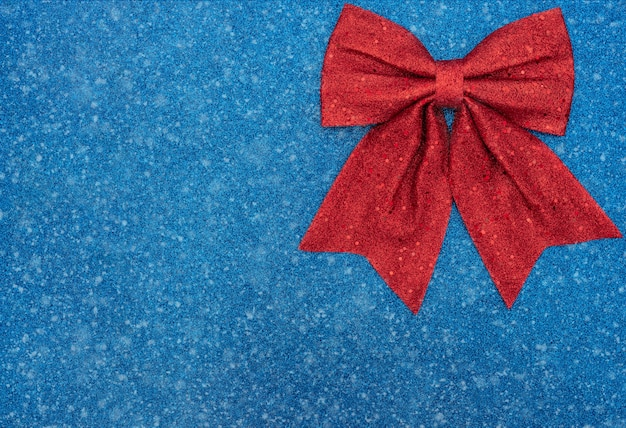 Fundo azul de natal ou inverno com laço vermelho e neve. natal, conceito de inverno. estilo liso leigo com espaço de cópia.
