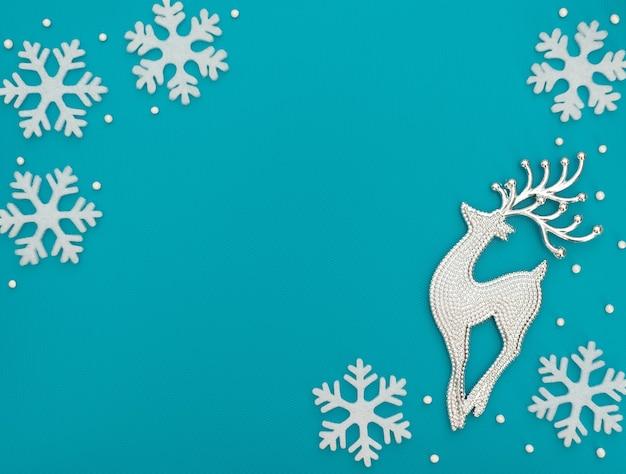 Fundo azul de natal ou inverno com um cervo e flocos de neve brancos e grânulos. estilo liso leigo com espaço de cópia.