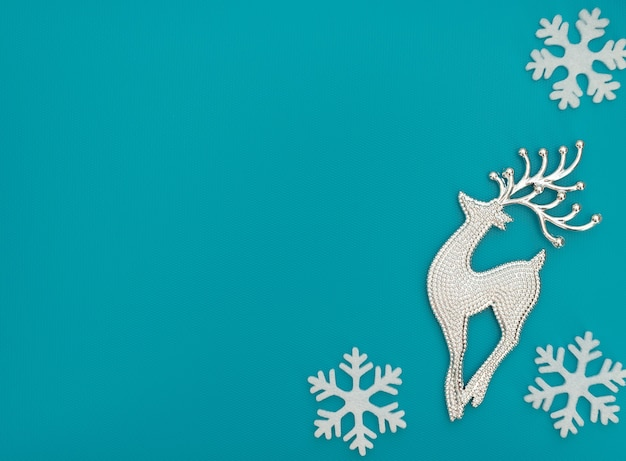 Fundo azul de natal ou inverno com um cervo e flocos de neve brancos. estilo liso leigo, copie o espaço.