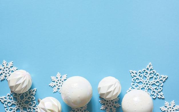 Fundo azul delicado de natal com bolas brancas. luzes de bokeh. decoração de ano novo. presentes.