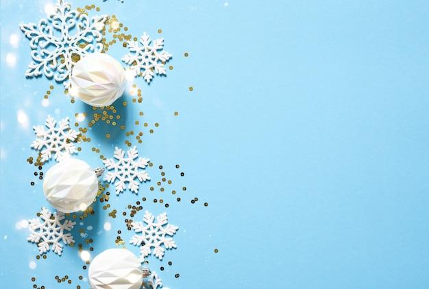 Fundo azul delicado de natal com bolas brancas. luzes de bokeh. decoração de ano novo.