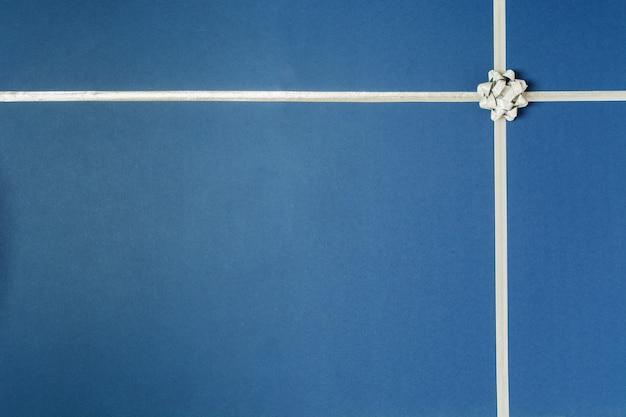 Fundo azul do feriado para presente com fita de prata e laço de prata