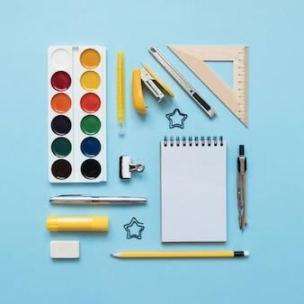 Fundo azul e material escolar amarelo