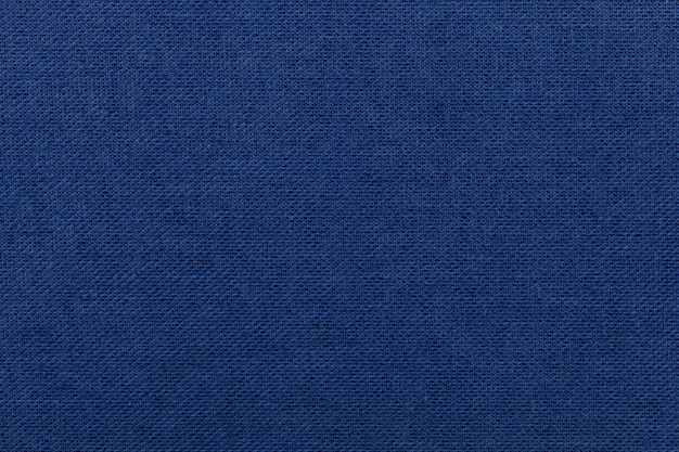 Fundo azul escuro de material têxtil. tecido com textura natural.