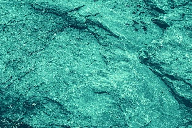Fundo azul vintage. parede áspera pintada de cor turquesa. plano imperfeito de cor ciano. decorativo velho desigual tonificado de tonalidade azul. textura de tonalidade verde-azulado. superfície pedregosa ornamental.