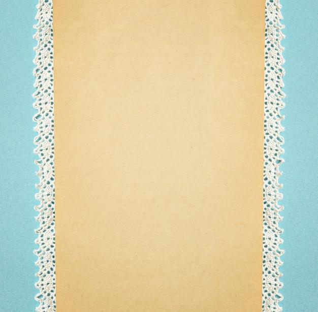 Fundo bege com renda e uma faixa de papelão azul nas bordas