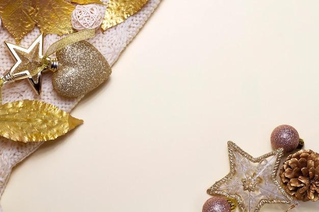 Fundo bege de natal com brinquedos dourados, suéter tricotado, folhas douradas, estrelas e balões