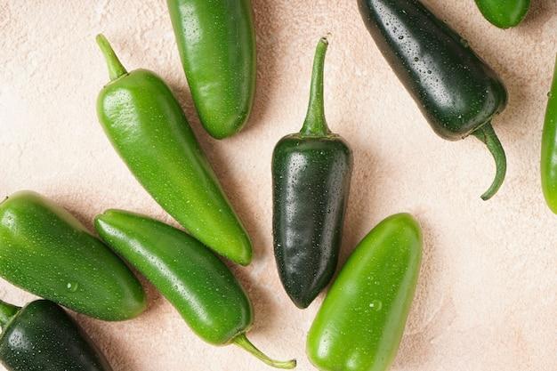 Fundo bege de pimentas jalapeno verde, close-up. postura plana.