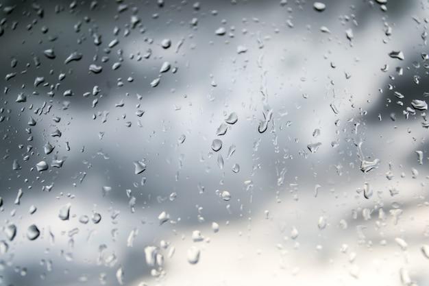 Fundo bonito da natureza chovendo e gota de orvalho no vidro.