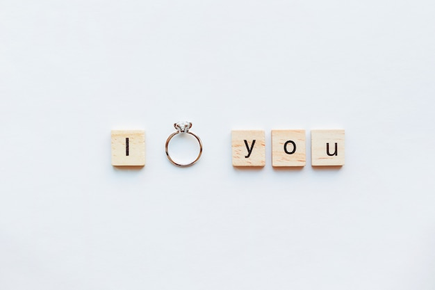 Fundo branco com palavras de madeira eu te amo e anel de noivado de diamante.