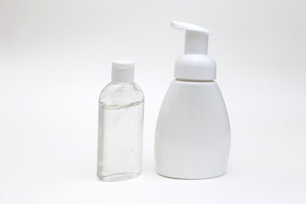 Fundo branco com uma garrafa branca de sabão antibacteriano e gel antibacteriano para as mãos