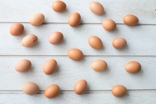 Fundo branco da textura da mesa de cozinha com os ovos frescos ajustados.