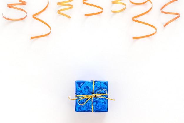 Fundo branco de celebração com caixa de presente azul com fita dourada, flâmulas de festa brilhantes.