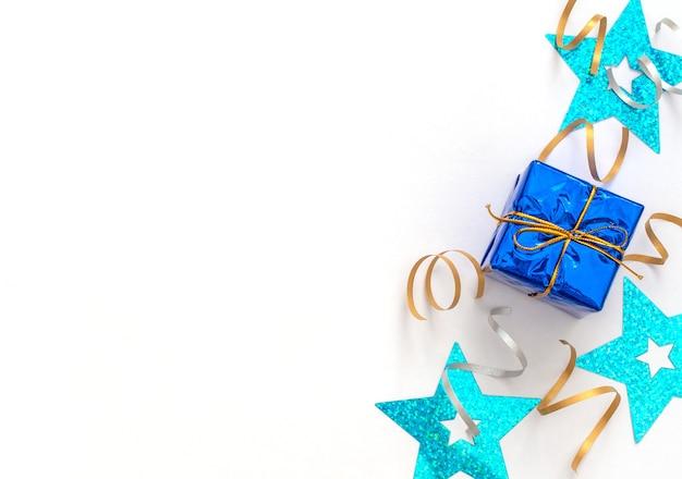 Fundo branco de celebração com caixa de presente com fita dourada, flâmulas de festa brilhantes e estrelas azuis.