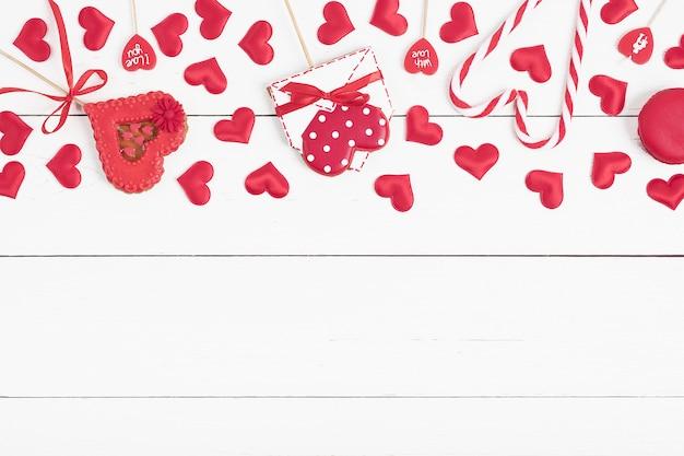 Fundo branco de madeira com pão de mel vermelho em forma de letras e corações