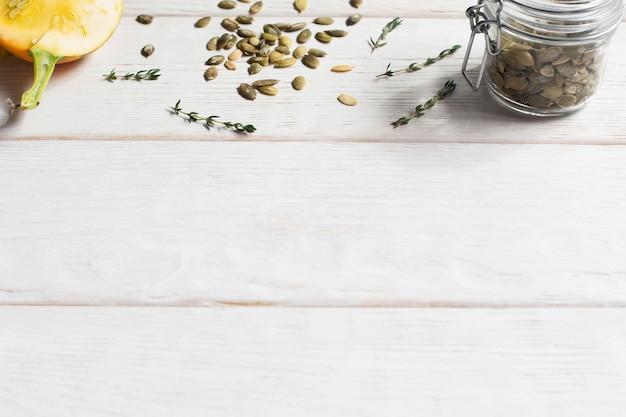 Fundo branco de madeira com sementes de abóbora
