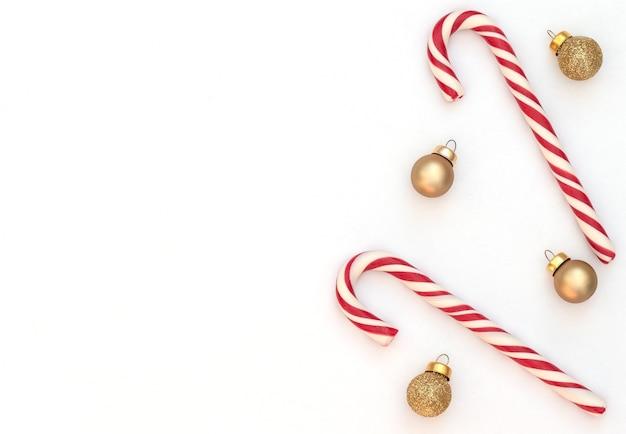 Fundo branco de natal com dois bastões de doces e bolas de natal douradas. estilo liso leigo, copie o espaço.