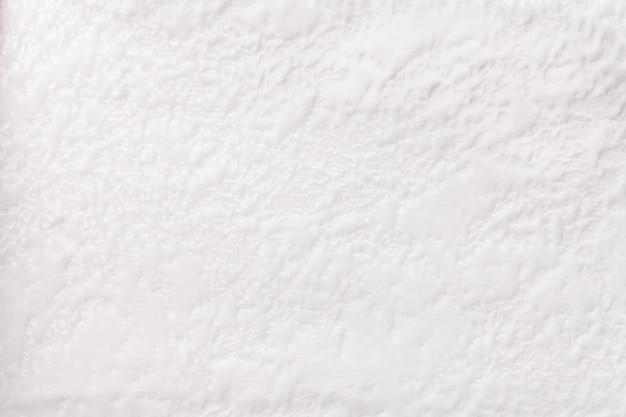 Fundo branco de um material têxtil de estofamento macio, closeup.