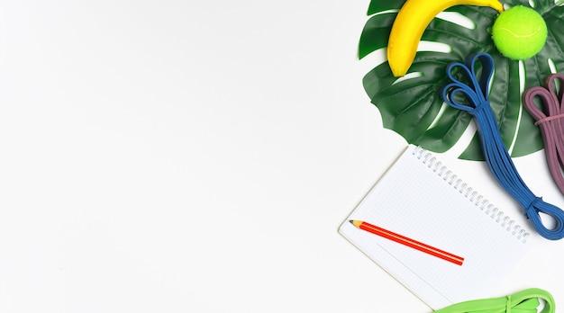 Fundo branco e loop de resistência para exercícios, caderno para plano de exercícios e resultados, postura plana