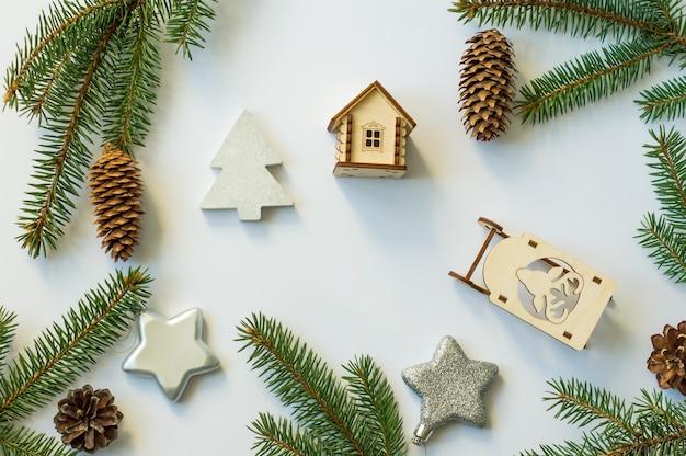 Fundo branco festivo com ramos de abeto, cones, estrelas de prata e brinquedos de madeira. vista do topo.