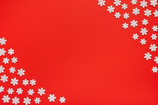 Fundo brilhante de férias, flocos de neve brancos sobre fundo vermelho, conceito de feliz natal e feliz ano novo, lay-out plana, vista superior, espaço de cópia