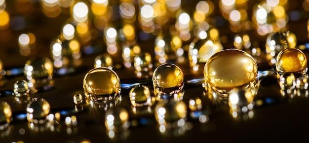 Fundo brilhante dourado com gotas, na superfície preta. macro de partículas de brilho dourado. fundo abstrato luxuoso.