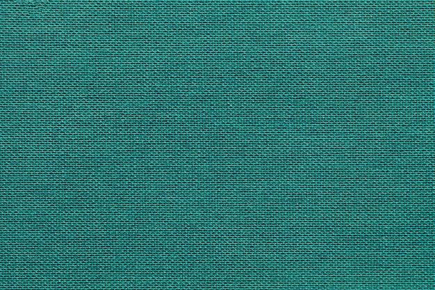 Fundo ciano claro de um material de matéria têxtil com teste padrão de vime, close up.