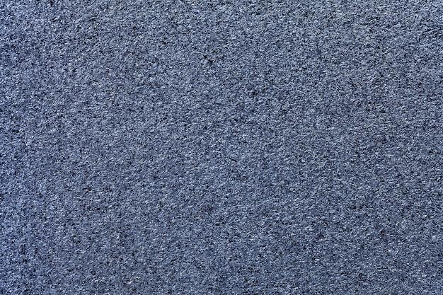 Fundo cintilante azul marinho de pequenas lantejoulas, closeup. cenário de papel metálico jeans de folha. bancada da superfície da cozinha, macro.