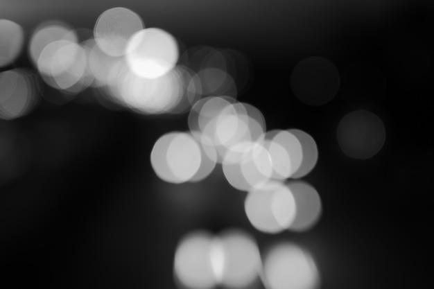 Fundo cinza bokeh. feliz ano novo 2022. efeito abstrato preto e branco luz noite fora do papel de parede do círculo de foco. para feriados de celebração de festa de natal ou conceito de fundo de coração partido.