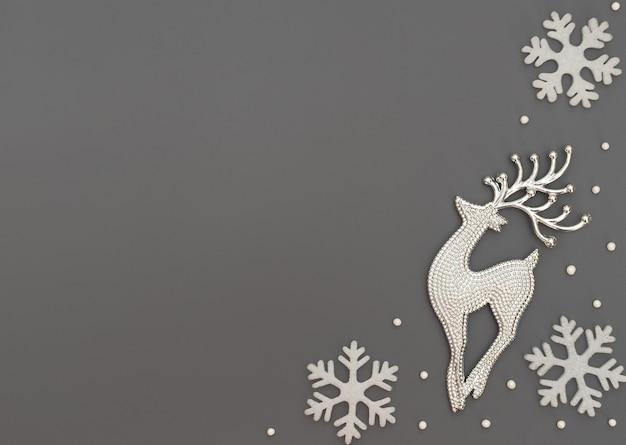 Fundo cinza de natal ou inverno com um cervo e flocos de neve brancos e miçangas