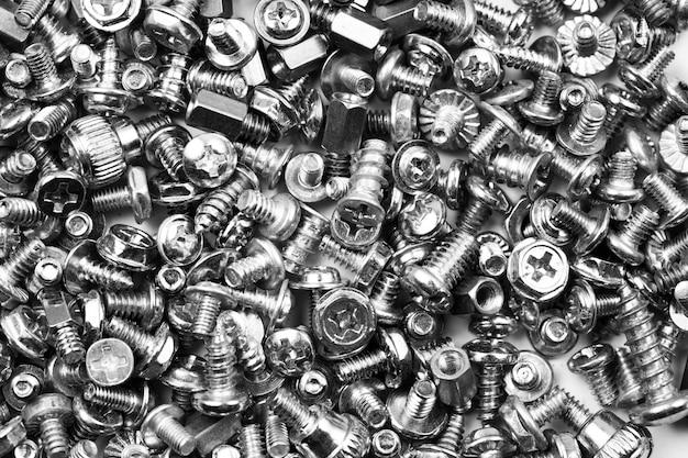 Fundo cinza textura de muitos parafusos de computador espalhados aleatoriamente