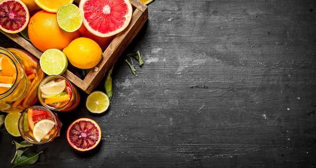 Fundo cítrico. suco cítrico fresco com fatias de limão, laranja, toranja e limão. no quadro negro.