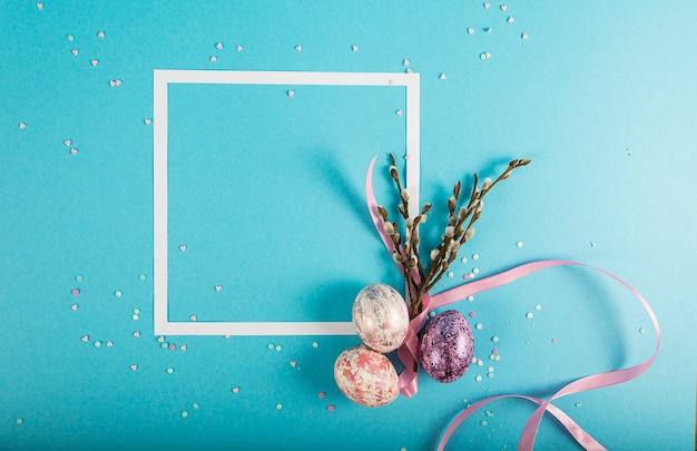 Fundo colorido com moldura, ovos de páscoa em fundo azul. conceito de feliz páscoa.
